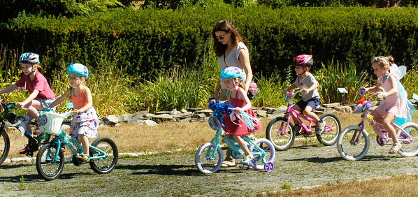 BRYAN EATON/Staff photo. Youngsters proceed around Atkinson Common in the Bike and Doll Carriage Parade in Kids Day in the Park.