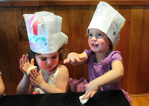 Newburyport: Carolyn Silva, left, and Helen Brown, both 3, roll out pizza dough at Anchor Stone Deck Pizza in Newburyport. Children from the Newburyport Montessori School went there on a field trip to learn how pizza is made and got to eat the demonstrations. Bryan Eaton/Staff Photo