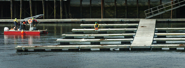 Newburyport: Workers continue to install docks along at the Merrimack River as the days get warmer. Here on Monday some were worked on in front of Michael's Harborside in Newburyport. Bryan Eaton/Staff Photo