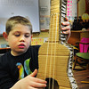 Newbury: Mason Martinello, 8, demonstrates a guitar he made of various pieces of cardboard and rubber bands. Third-graders at Newbury Elementary School are celebrating Earth Day and with their study of sound, some students of have taken a cue from Landfill Harmonic, the documentary being created in Paraguay, and have created instruments out of recycled materials as the people have done at the landfill in that country. Bryan Eaton/Staff Photo
