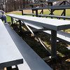 Salisbury: Lee-Anne Merenda paints a set of bleachers at Lion's Park in Salisbury on Monday as her husband, Rob, a coach for the Salisbury Little League scraped paint of another. They were readying for opening day this Saturday that begins with a parade at the Hilton Center and ends at the park. Bryan Eaton/Staff Photo