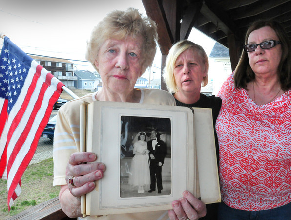 Salisbury: Doris Steinel Fisette, with daughters Barbara Steinel, center, and Mary Steinel-Andriotakis, holds the wedding photo of her and her late husband, Robert, at the East Parish United Methodist Church. Her husband was one of the crewman on the submarine USS Thresher out of Portsmouth, N.H. which sunk off Cape Cod 50 years ago today during testing. Bryan Eaton/Staff Photo
