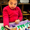 """Salisbury: Isabella Bazdanes, 6, creates a self-portrait in a setting of grass and spring flowers at Salisbury Elementary School on Thursday. The kindergartners in Kathleen Orroth's class were in """"work station time"""" where they can work on projects of their choosing. Bryan Eaton/Staff Photo"""