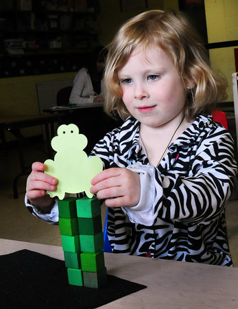 Amesbury: Alyssa LeBrun, 5, puts a frog atop some blocks she piled up during kindergarten screening at Amesbury Elementary School on Thursday. She was spending time with screener Alli Mroz, while her mom filled out paperwork in another room, getting acquainted with the school environment. Bryan Eaton/Staff Photo