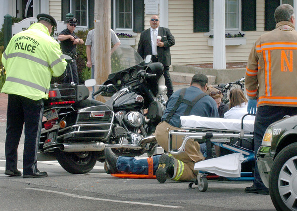 Newburyport: Medics attend a man with minor injuries in a motorcycle accident on Green Street in Newburyport yesterday morning. Bryan Eaton/Staff Photo