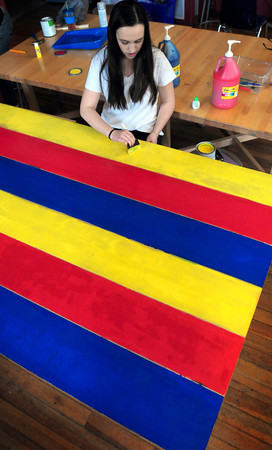 Newburyport: Maggie Mahoney, 14, paints a board different colors at the Kelley School Youth Center to be used for a horse racing game. Teens there are building different games to be used their Duck Derby May 5 at the Bartlet Mall to raise money for summer trips. Bryan Eaton/Staff Photo