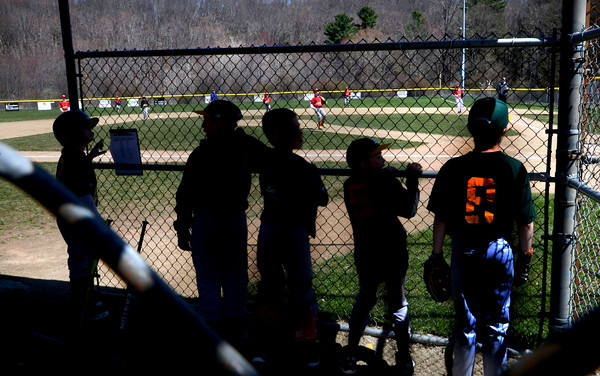 Amesbury: Members of the Amesbury Little League Athletics watch their game against the Cardinals on a bright cold opening day at the Cashman School Sunday. Opening day was scheduled for Saturday , but was postponed due to morning rain. Jim Vaiknoras/staff photo
