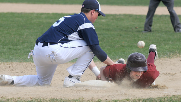 NEWBURYPORT: Triton's Adam Chatterton tries to make a play as the ball boundes off of Newburyport's Brian Fiascone's head as he dives back to first base during their game at Pettingell Field in Newburyport. Jim Vaiknoras/staff photo