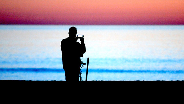 Salisbury: A man with a metal detector on Salisbury Beach pauses to use his cell phone to photograph the rising sun Sunday . Jim Vaiknoras.staff photo