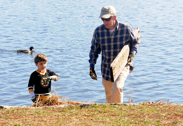 JIM VAIKNORAS/Staff photo Luke Witner, 4, and his dad Dan clean up along teh Merrimack River in Newburyport Saturday. They were amounst the more than 50 volunteers to help out in the annual Clean Sweep through out Newburyport.