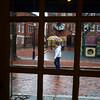 JIM VAIKNORAS/Staff photo A woman walking in the rain on Inn Street in Newburyport is framed in the doorway of the Purple Onion Saturday afternoon