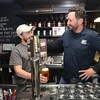 JIM VAIKNORAS/Staff photo. Bill Fisher and Chris Web pour a glass of their new beer Melt Away at the Newburyport Brewing Company.