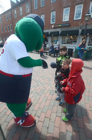 JIM VAIKNORAS/Staff photo   Wally the Green Monster sign hats for brothers Joseph, 9, TJ 4, and Patrick Skiba, 7, during his visit to Newburyport Saturday morning.