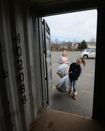 JIM VAIKNORAS/Staff photo.  Logan Lattime and Chloe Hansen load shoes in a trailer at the Nock Middle School library in Newburyport Friday. The Newburyport School community has been donated used shoes to the Shoeman Water project www.shoemanwaterorg since the beginning of March. Student at the Middle School have bound and bagged 2,400 pairs of shoes. Graf Brothers has donated a 40 ft trailer to store the shoes until the drive is over on May 1.