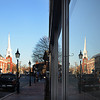 JIM VAIKNORAS/Staff photo Pleasent Street in Newburyport is mirrored in the window of Greta's early Sunday morning.