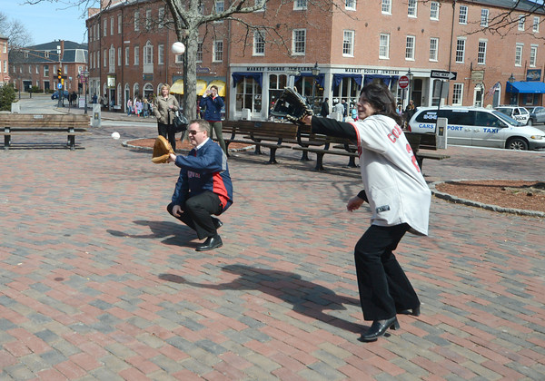 "JIM VAIKNORAS/Staff photo  <br /> MAyor Donna Holaday and Scott Eaton of Newburyport Five Cent Savings catch the "" First Pitch"" from players on the Newburyport high baseball and softball teams in Market Square in Newburyport Friday. The event was in honor of the Red Sox home opener."