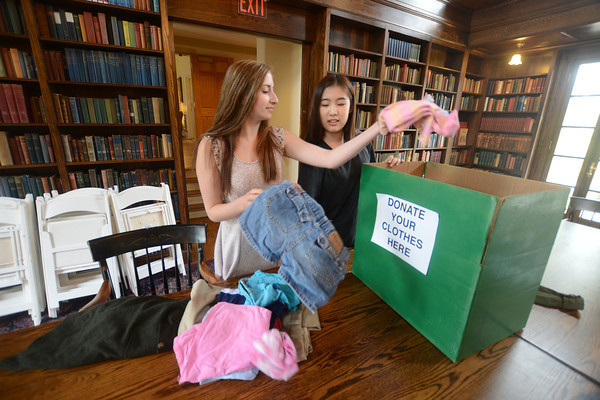 "JIM VAIKNORAS/Staff photo  Emmy Cole and Chloe Lee go through donations at the Governor's Academy. They are collecting clothes that their classmates don't want to pack up and bring home at the end of the year, and then hold a ""sale"" where kids can ""purchase"" the clothes, paying with canned goods and donations for the Salvation Army."