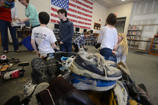 JIM VAIKNORAS/Staff photo.  Students sort through shoes in the Nock Middle School library in Newburyport Friday. The Newburyport School community has been donated used shoes to the Shoeman Water project www.shoemanwaterorg since the beginning of March. Student at the Middle School have bound and bagged 2,400 pairs of shoes. Graf Brothers has donated a 40 ft trailer to store the shoes until the drive is over on May 1.