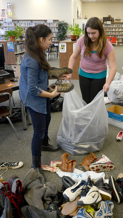 JIM VAIKNORAS/Staff photo.  Shantel Kelley and Angelica Soares bag shoes in the Nock Middle School library in Newburyport Friday. The Newburyport School community has been donated used shoes to the Shoeman Water project www.shoemanwaterorg since the beginning of March. Student at the Middle School have bound and bagged 2,400 pairs of shoes. Graf Brothers has donated a 40 ft trailer to store the shoes until the drive is over on May 1.