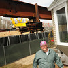 BRYAN EATON/Staff Photo. Scott Taylor heads up the back deck of his Amesbury home adjacent to the construction of the new Whittier Bridge.