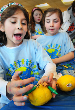 Newburyport: Ana Lynch, left, and Rita Cahalane, both 8, explain how lemons can be used as a battery which lit a small bulb. The two were at the Bresnahan School Science Fair on Thursday. Bryan Eaton/Staff Photo
