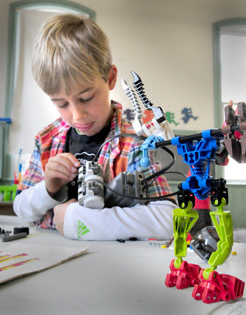 """BRYAN EATON/ Staff Photo. Ben Pike, 7, works on a robotic Lego """"rover"""" at the Kelley School Youth Center on Wednesday. He and others were creating different contraptions with the help of Kevin Husson, in one of the programs by Newburyport Youth Services during school vacation."""