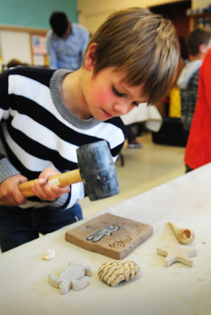 BRYAN EATON/ Staff Photo. Dante Chabot, 6, taps different molds into a clay tile, to be later dried and glazed in a kiln, at the Brown School in Newburyport. The students were working with staff from the Symmetry Tile Works funded by the Newburyport Education Foundation through a grant written by teacher Melissa Duguie.