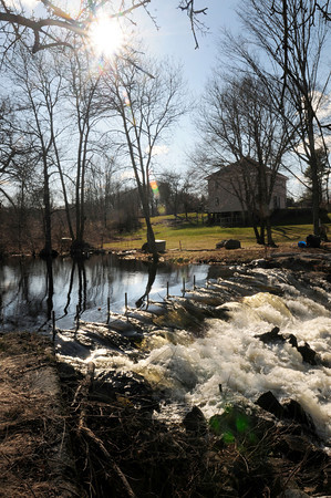BRYAN EATON/Staff Photo. Sunlight reflects off heavy water flow of the Parker River at Central Street in Byfield on Wednesday afternoon.