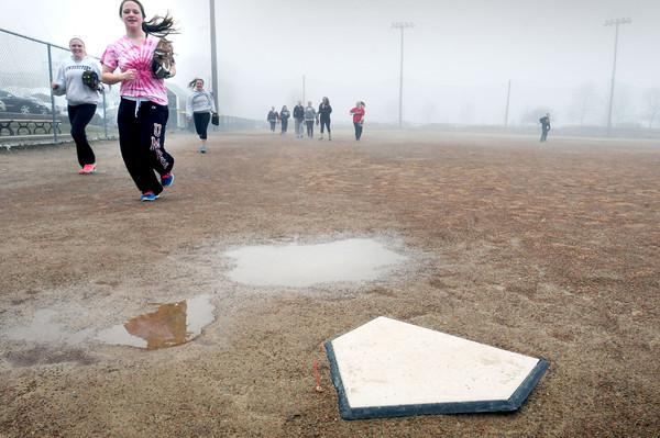 BRYAN EATON/Staff Photo. The Newburyport High softball team practice around puddles at the ballfield at Cashman Park.