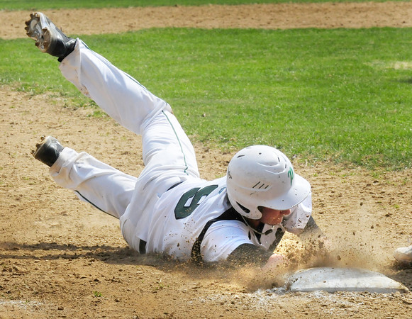 BRYAN EATON/ Staff Photo. Pentucket's Ian Davis kicks up the dirt as he makes it safely to third base.