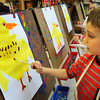 "BRYAN EATON/ Staff Photo. Miles Bickel, 6, paints a duckling using paintbrushes and a sponge in Pam Jamison's art class at the Brown School in Newburyport on Tuesday. The children read the book ""Fuzzy Ducklings"" and painted the character of the book learning about texture and color."