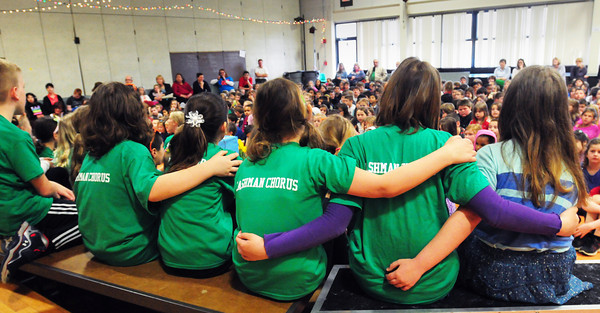 """BRYAN EATON/ Staff Photo. Students embrace as they sing """"Rainbow Connection"""" at the Cashman School in Amesbury yesterday before the school body. The school's chorus was performing their spring concert themed The Lion's Pride."""