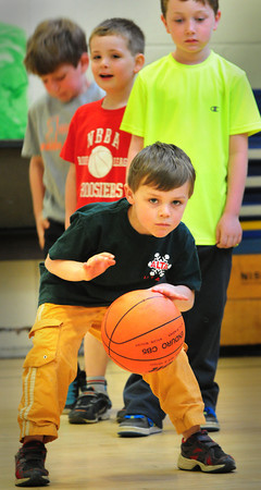 BRYAN EATON/ Staff Photo. With the look of determination Connor Cronin, 5, takes his turn at dribbling a basketball at the Brown School gym on Wednesday. He was in a sports camp sponsored by Newburyport Youth Services during this week's school vacation.