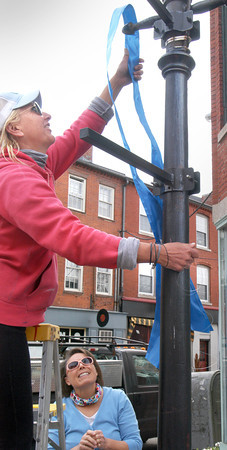 """BRYAN EATON/ Staff Photo. Volunteer Jen Wright hangs blue ribbon on a lamppost in downtown Newburyport as Exchange Club president Mary Sortal looks on. The club, with city permission, attached ribbons around the downtown recognizing April as """"Child Abuse Prevention Month."""""""
