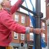 "BRYAN EATON/ Staff Photo. Volunteer Jen Wright hangs blue ribbon on a lamppost in downtown Newburyport as Exchange Club president Mary Sortal looks on. The club, with city permission, attached ribbons around the downtown recognizing April as ""Child Abuse Prevention Month."""