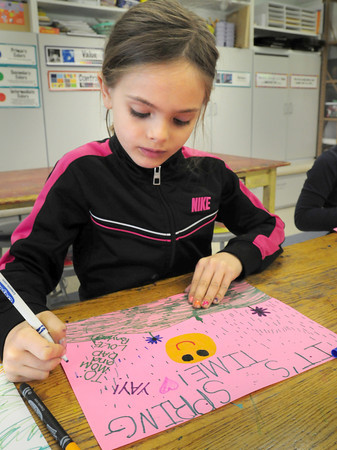 """BRYAN EATON/ Staff Photo. Bayleigh Shanahan, 7, works on a free time art project where she painted a scene that said """"It's Spring Time"""" which it seems to be anything but outside. She was in Sara Connor's art class at the Amesbury Elementary School on Tuesday morning."""