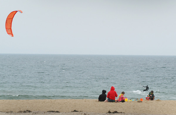 BRYAN EATON/ Staff Photo. A kite boarder has an audience at Salisbury Beach State Reservation on Tuesday afternoon. An offshore breeze kept temperatures cooler on the immediate coast.