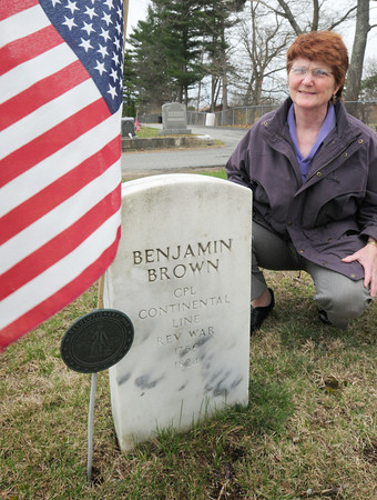 BRYAN EATON/ Staff Photo. Ann Robinson at the grave of Benjamin Brown, who was a corporal in the Continental Line in the Revolutionary War, at the Smithtown/Methodist/Hillside Cemetery in Seabrook.