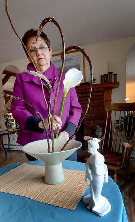 "BRYAN EATON/Staff Photo. Carol Gura works on a floral display inspired by ""Memoirs of a Geisha."""