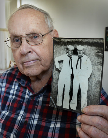 BRYAN EATON/Staff Photo. World War II navy veteran Bill Ryan of Amesbury shows a photo of himself, right, with a fellow sailor whose last name was Bowmand in Pearl Harbor on August 11, 1944.
