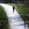 BRYAN EATON/Staff Photo. A bicyclist heads south along the Clipper City Rail Trail past some daffodils in a view from the High Street Bridge. The trail should be a busy spot this weekend as temperatures get into the 60's and 70's.
