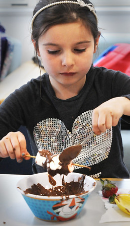 BRYAN EATON/Staff Photo. Riley McIsaac, 7, drizzles melted chocolate onto bananas and marshmallow at Salisbury Elementary School. She was in the popular Sweet Treats class at the afterschool program Explorations.