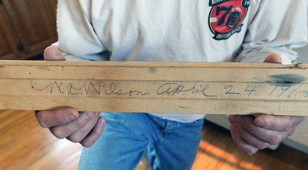 BRYAN EATON/Staff Photo. Mike Madden who acquired floorboards from a salvaged home in Amesbury that had burned has been used to lay in his Merrimac home. On the back of one of the boards was penciled the date April 24, 1916 apparently when the original floor was laid maybe by W.A. Wilson.