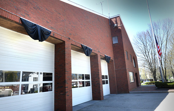 BRYAN EATON/Staff Photo. The flag is at half staff and black bunting is over the bay doors of the Newburyport Fire Department in honor of firefighter Tony Raven, who died this week.