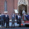BRYAN EATON/Staff Photo. Area firefighters and other mourners file into the Immaculate Conception Church yesterday afternoon to pay their respects during the wake of Newburyport firefighter Tony Raven who died on Tuesday. A funeral Mass will be celebrated there today at 1:30 p.m.