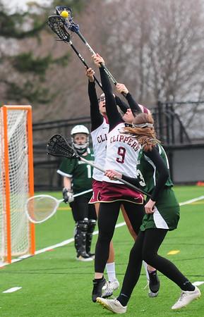 JIM VAIKNORAS/Staff photo Newburyport girls lacrosse player #9 and #15 reach for the ball against Bonny Eagle at Newburyport.