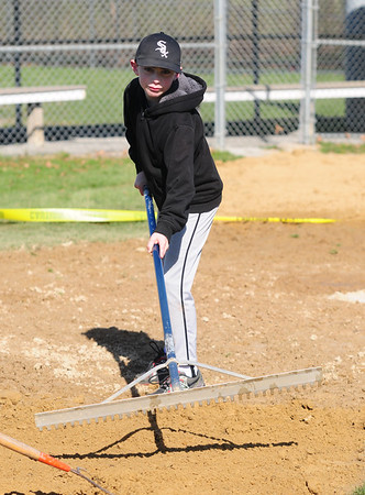 JIM VAIKNORAS/Staff photo Shain Parisella , 10 rakes the infield  at the Little League field at the Cashman School in Amesbury Saturday.