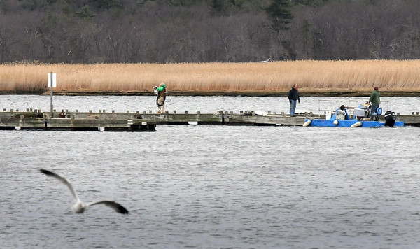 BRYAN EATON/Staff Photo. Several docks went in to the Merrimack River several weeks ago during some warm weather. With temperatures on the rise again more docks are going in, here at the North End Boat Club in Newburyport.