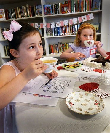 BRYAN EATON/Staff Photo. With pinkies extended Alexa Warchol, left, and Kaeleigh Belanger, both 7, sip apple tea at the Emma Andrews Library in Newburyport on Tuesday. They were at the Alice in Wonderland Dress-up Tea which included stories and craft-making during school vacation week.