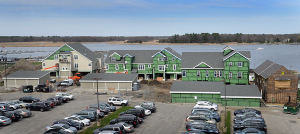 BRYAN EATON/Staff Photo. Luxury condos under construction on the Merrimack River behin the Towle Building.